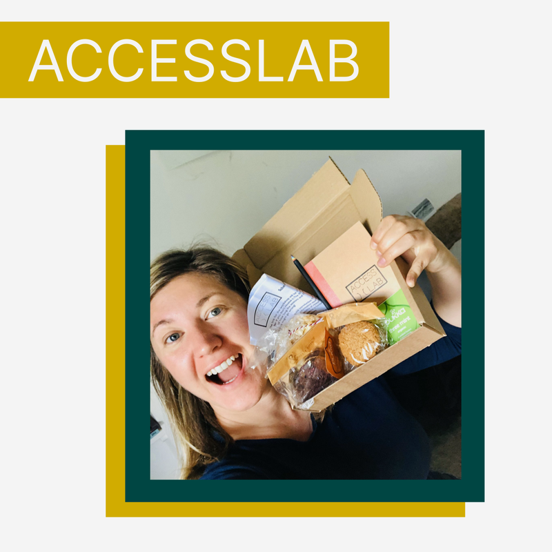 AccessLab image, with a participant grinning holding a small card box containing various biscuits, notebook, pencil, tea etc. which were sent out to all participants.