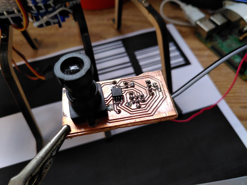 The sensor printed circuit board with lens in place and test patterns in the background