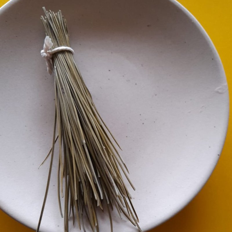 Bundle of dried pine needles tied with string, on a plate.